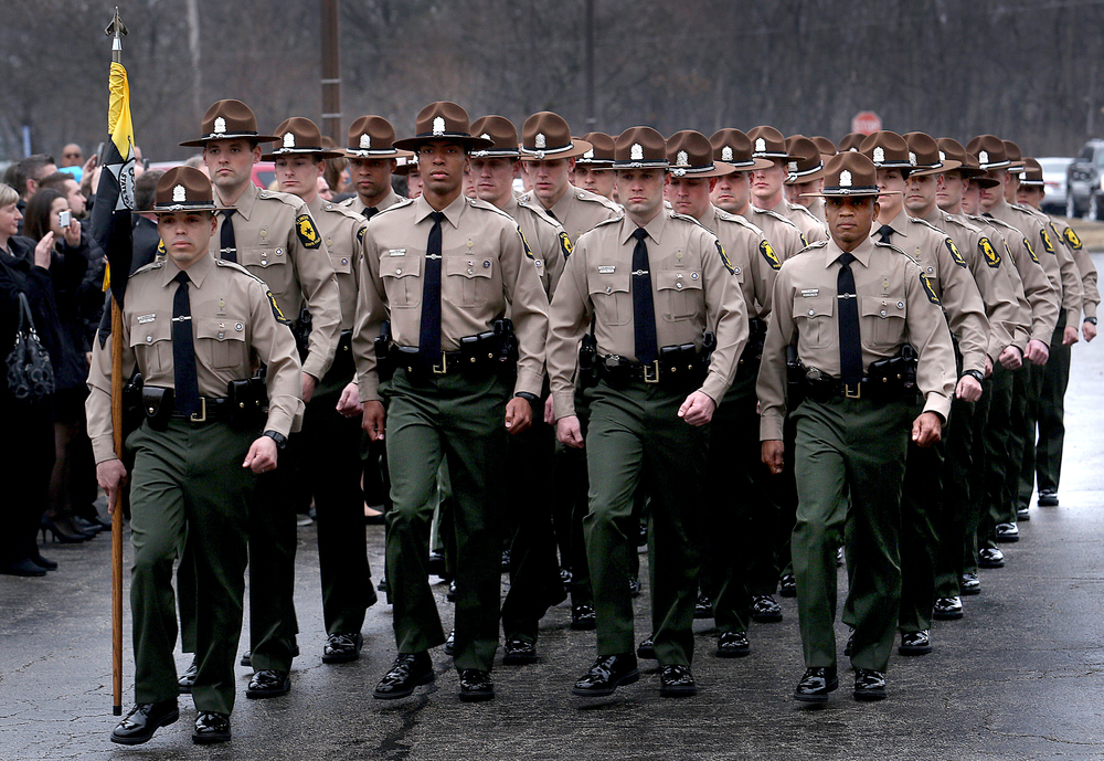 Members of Cadet Class 125, lead by Illinois State Police Trooper Enrique Barrientos holding the Guidon at left, march in formation before taking part in the Bell Ceremony outside the Academy Friday morning.  David Spencer/The State Journal-Register