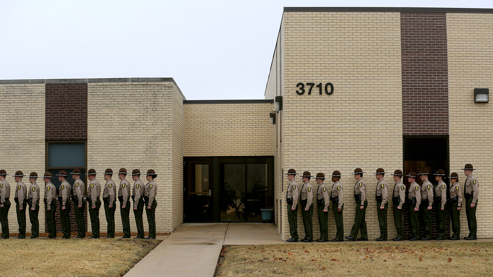 "New Illinois State Troopers stand in formation alongside the Police Academy building while making their way to the front of the line where they would each ring a large brass bell, described by the Academy as a ""glimpse into the tradition and honor of an ISP Trooper.""  David Spencer/The State Journal-Register"