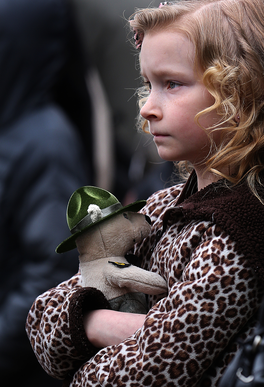 Alayna Ushman, 8, whose uncle Joshua Ushman was the President for Cadet Class 125, clutches an Illinois State Police teddy bear while watching the formal Bell Ceremony Friday morning.  David Spencer/The State Journal-Register