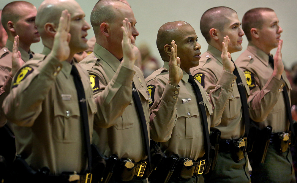 Illinois State Police troopers raise their hands while taking their official oath Friday morning.  David Spencer/The State Journal-Register