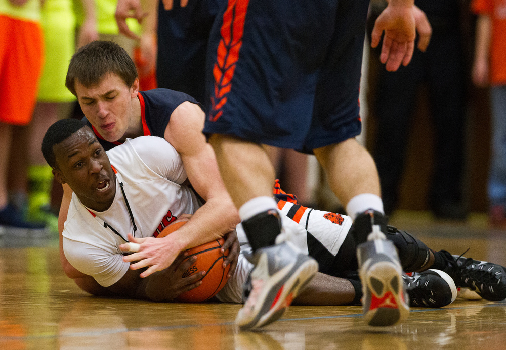 Lanphier's Jordan Tribbet (12) forces a jump ball as he dives on a loose ball against Mahomet-Seymour's Conner Diedrich (25) in the second half during the Class 3A Champaign Centennial Sectional title game, Friday, March 13, 2015, in Champaign, Ill. Justin L. Fowler/The State Journal-Register
