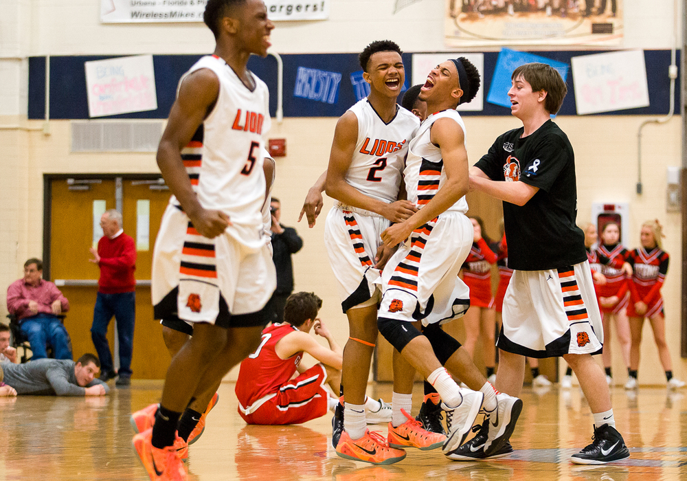 Lanphier's Cardell McGee (2) is mobbed by his teammates after Lanpheir defeated Glenwood 44-42 in the Class 3A Champaign Centennial Sectional semifinals, Tuesday, March 10, 2015, in Champaign, Ill. Justin L. Fowler/The State Journal-Register