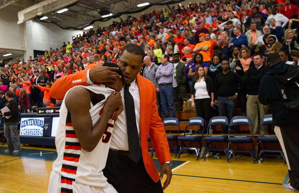 Lanphier head coach Blake Turner comforts Lanphier's Xavier Bishop (5) after the Lions were defeated 71-70 by Mahomet-Seymour in the Class 3A Champaign Centennial Sectional title game, Friday, March 13, 2015, in Champaign, Ill. Justin L. Fowler/The State Journal-Register