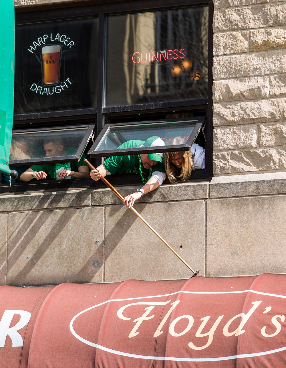 A pool bridge stick is used to grab an item off the top of the awning from the second floor of Floyd's during the 2015 Saint Patrick's Day Parade, Saturday, March 14, 2015, in Springfield, Ill. Justin L. Fowler/The State Journal-Register