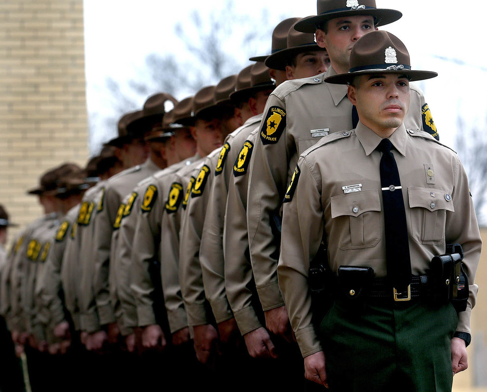 "Illinois State PoliceTrooper Enrique Barrientos, who will be assigned to the District 2 office in Elgin, stands at the front of the line of new troopers who would soon ring the bell as part of the formal ""Bell Ceremony"". Cadet Class 125, made up of 37 new Illinois State Police troopers, received their badges in a graduation ceremony at the Illinois State Police Academy in Springfield on Friday, March 13, 2015. The new troopers completed a 26-week program at the academy and will report to State Police district offices around the state where they will train with Field Training Officers for an additional 14 weeks before advancing to solo-patrol status. David Spencer/The State Journal-Register"