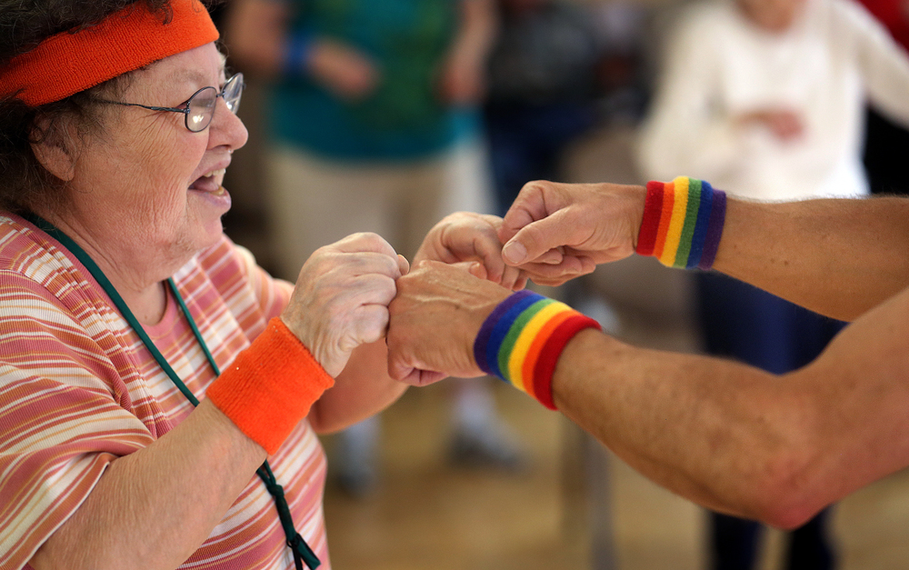"Resident Doreen Wolford, left, gets a fist bump from John Power, aka: ""Richard Simmons,"" during an exercise class on Monday, March 16, 2015. David Spencer/The State Journal-Register"
