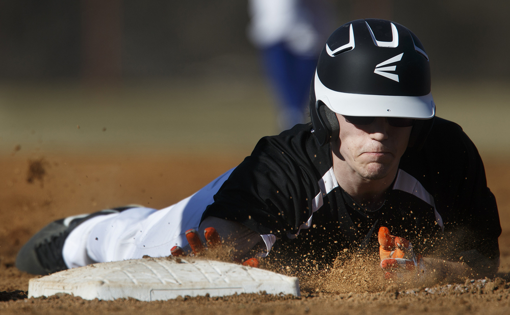 Lanphier's Alex Fuchs slides safely back into first base against Auburn at Lincoln Land Community College Monday, March 16, 2015. Ted Schurter/The State Journal-Register