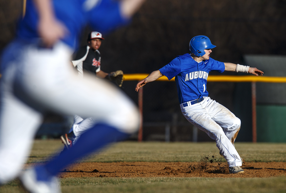 Auburn's Caleb Putman skids to a stop as he gets caught between first and second base as his teammate runs for home against Lanphier at Lincoln Land Community College Monday, March 16, 2015. Ted Schurter/The State Journal-Register