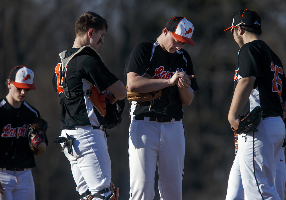 Lanphier's Jerry Nataut looks down as his teammates and coach approach the mound after he hit an Auburn player with a pitch at Lincoln Land Community College Monday, March 16, 2015. Ted Schurter/The State Journal-Register