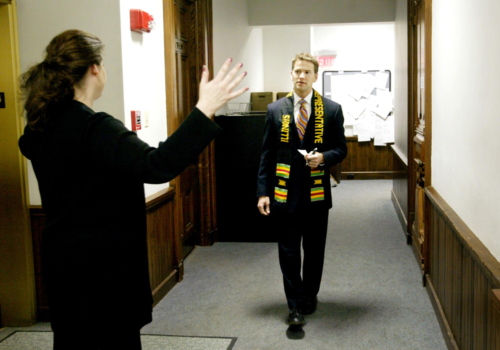 "State Rep. Aaron Schock talks with his Springfield administrative assistant, Paula O'Brien, before introducing Peoria's Roosevelt Magnet School for the Performing Arts choir on the House floor on March 2, 2005. ""She usually knows what I'm doing before I do,"" Schock said of O'Brien. Schock is wearing a stole given to legislators by the Illinois Legislative Black Caucus in celebration of Black History Month. File/The State Journal-Register."