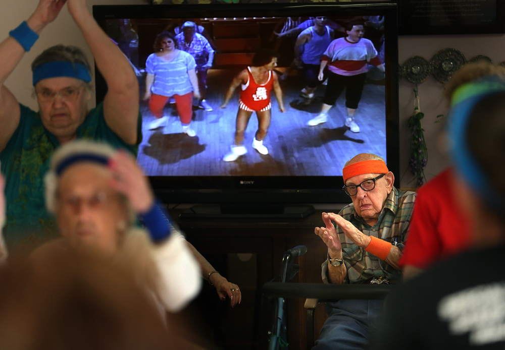 From his seat in front of the large television showing the Richard Simmons video, resident Don Cook, 89, moves to the music during the exercise class on Monday, March 16, 2015. David Spencer/The State Journal-Register