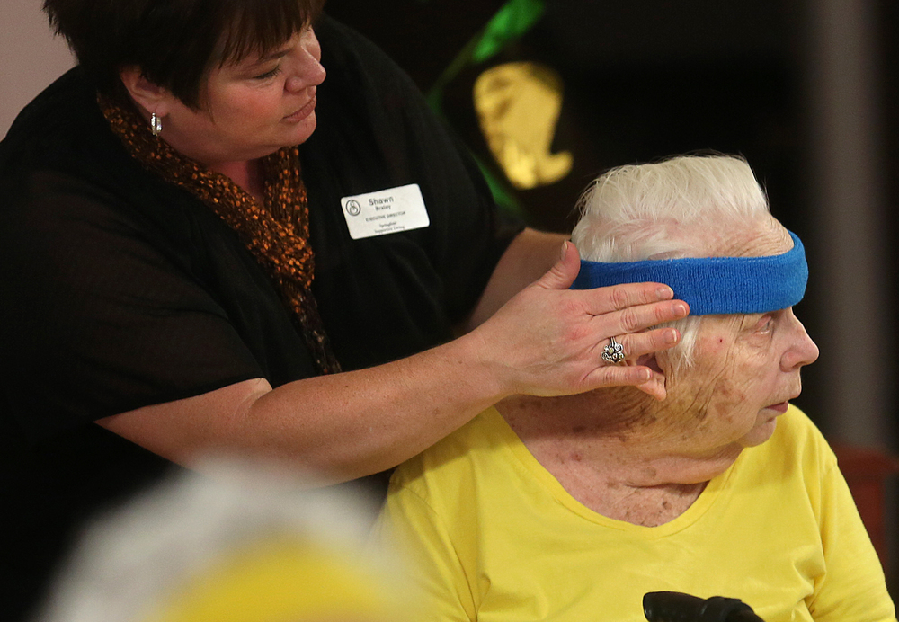 Each resident taking the class wears their own color-coordinated headband and wrist bands. During a water break, Supportive Living Executive Director Shawn Braley helps adjusts the headband worn by resident Donna Luke on Monday, March 16, 2015. David Spencer/The State Journal-Register