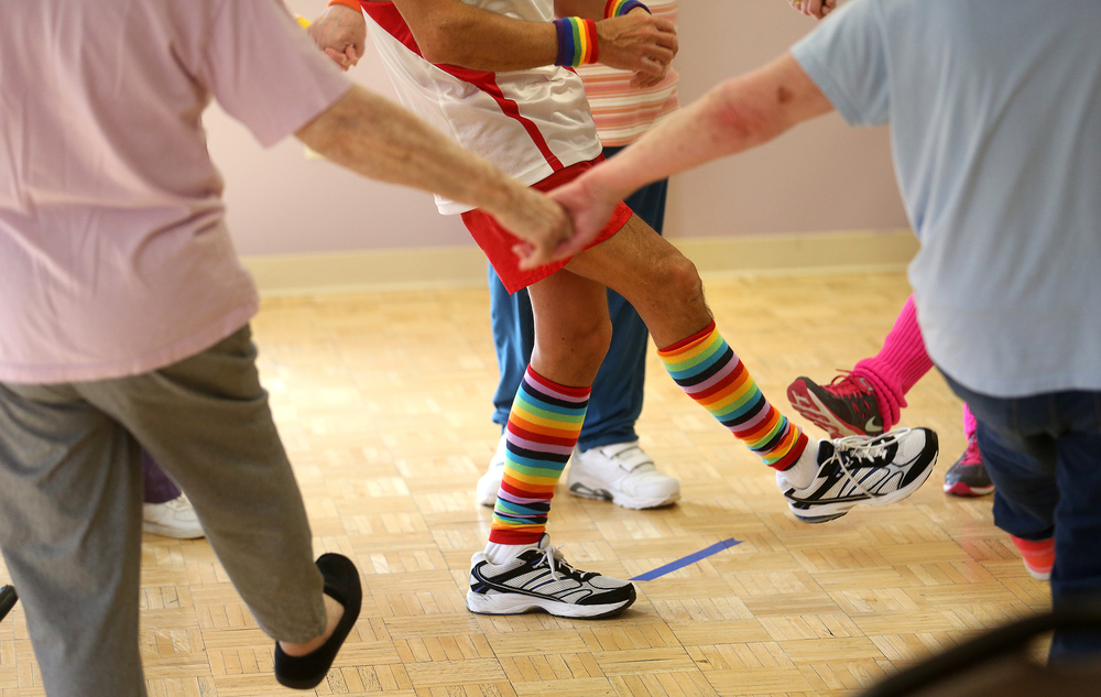 "Keeping the arms and legs moving is one of the exercise goals for residents taking the class. ""Richard Simmons,"" aka John Power, wears his rainbow socks while leading the class on Monday, March 16, 2015.  David Spencer/The State Journal-Register"