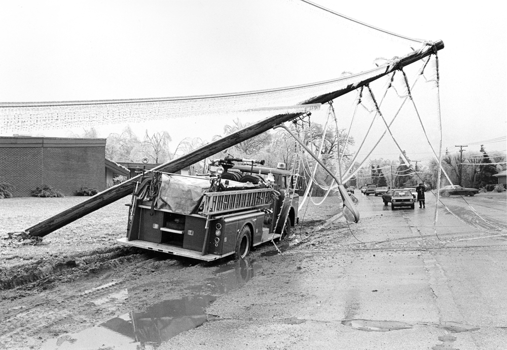 A firetruck at Jefferson Street and Churchill Drive was rendered useless when a utility pole fell on it, March 1978.
