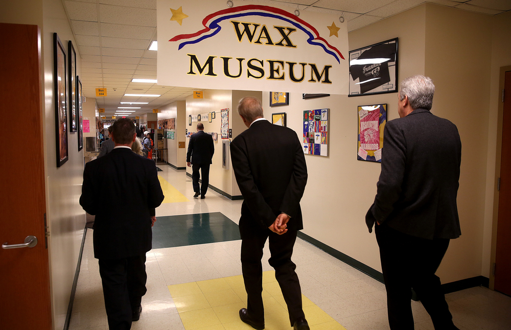 Gov. Rauner ducks slightly underneath a sign while headed to the wax museum at the school Tuesday morning. David Spencer/The State Journal-Register