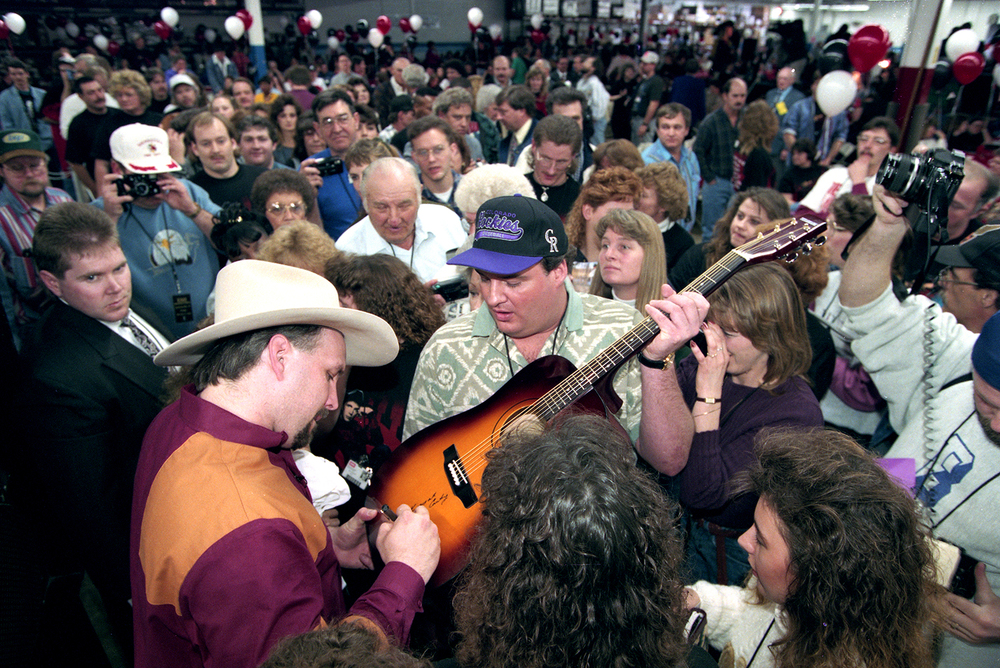 Garth Brooks signs a guitar while visiting with employees during a tour of the EMI Manufacturing plant in Jacksonville March 1995. File/The State Journal-Register