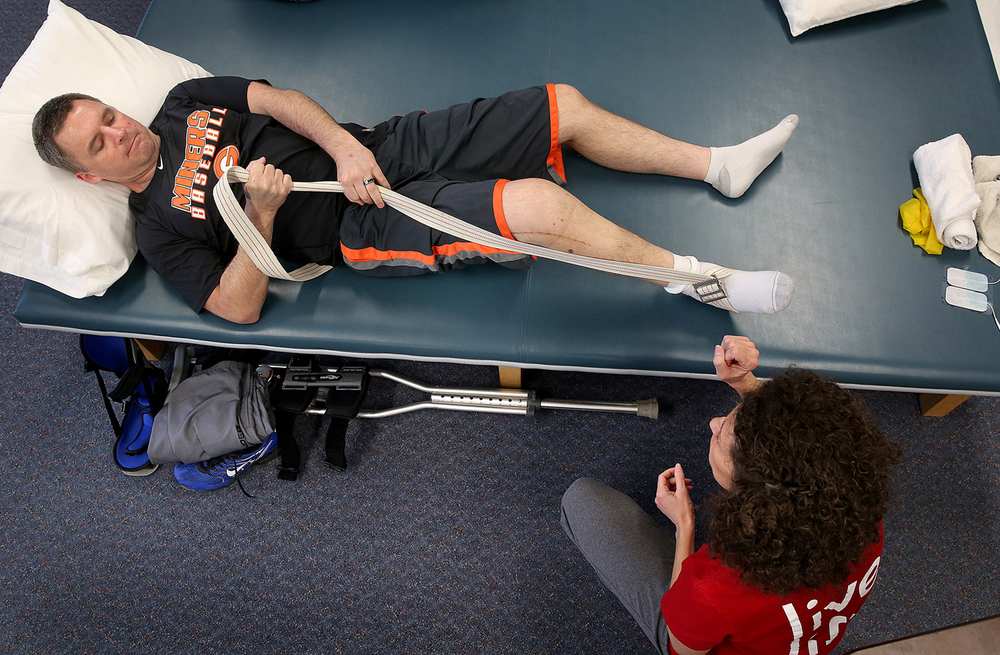 With the goal of strengthening his leg after recent knee reconstruction surgery, Randy Redmon pulls on a strap-one of a series of exercises he was doing Friday under the supervision of Physical Therapist assistant Jamie Gansz at right to increase his strength-one of a series of exercises he did on Friday. Randy and Amanda Redmon of rural Gillespie continue to recover after being hit by a drunken driver in August 2014 after being knocked off the motorcycle they were riding in Macoupin County. On Friday, March 27, 2015, Randy Redmon underwent one of his three weekly physical therapy sessions at ApexNetwork Physical Therapy in Gillespie. David Spencer/The State Journal-Register