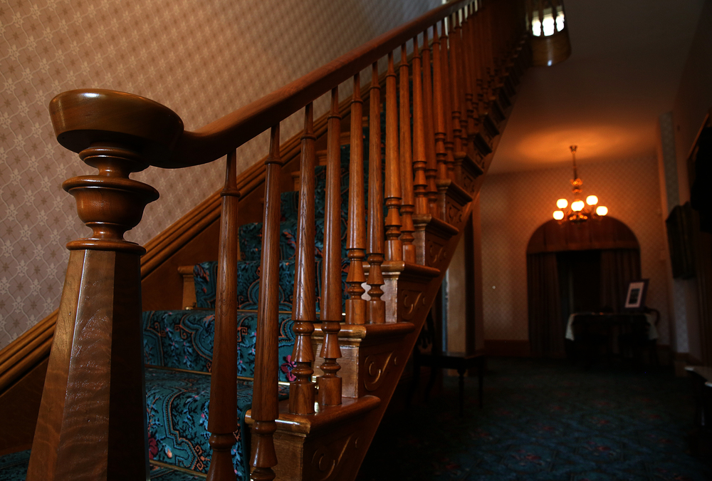 The ornate walnut and oak staircase has been restored, with a closet built in 1930 underneath removed completely along with the installation of new carpet partially secured with period brass stair roads for each step.  David Spencer/The State Journal-Register