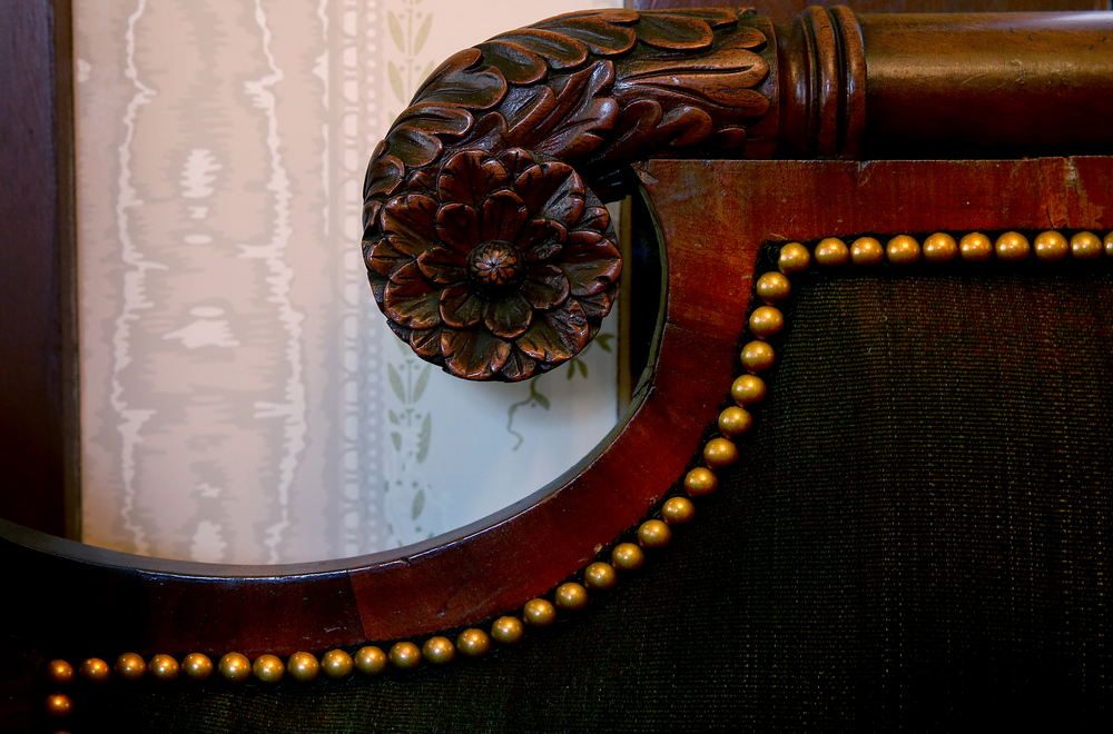 Antique furniture is a highlight of the renovation. This detail shows an ornamental hand-carved flourish made from walnut accented by brass tacks holding in place upholstery on a ca. 1820 couch owned by Governor Ninian Edwards on display in the library. David Spencer/The State Journal-Register
