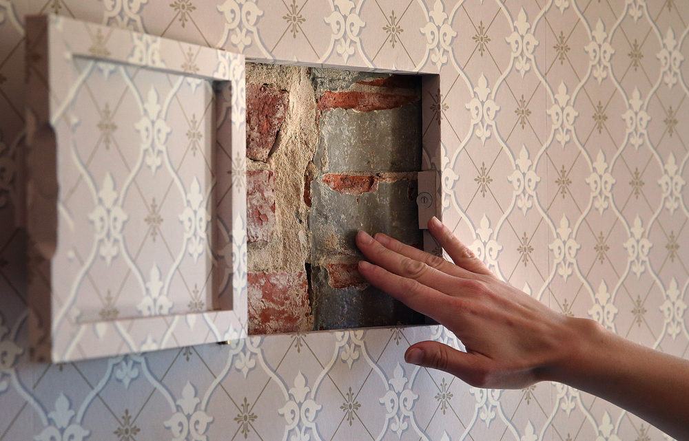 "Curator Erika Holst points out some of the original exterior brickwork of the home in this ""secret compartment"" built into the wall of the front foyer designed during the renovation to give visitors a window into the home's past.  David Spencer/The State Journal-Register"