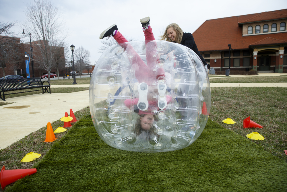 Nicole Lufkin rights her daughter Sienna St. Cin after she became stuck upside down in a Bubble Ball during the Egg Roll in the Park at Union Square Park Sunday, March 29. The event featured face-painting and tattoo stations, 19th century games, crafts, a photo booth in the shape of an egg, and free food. Ted Schurter/The State Journal-Register