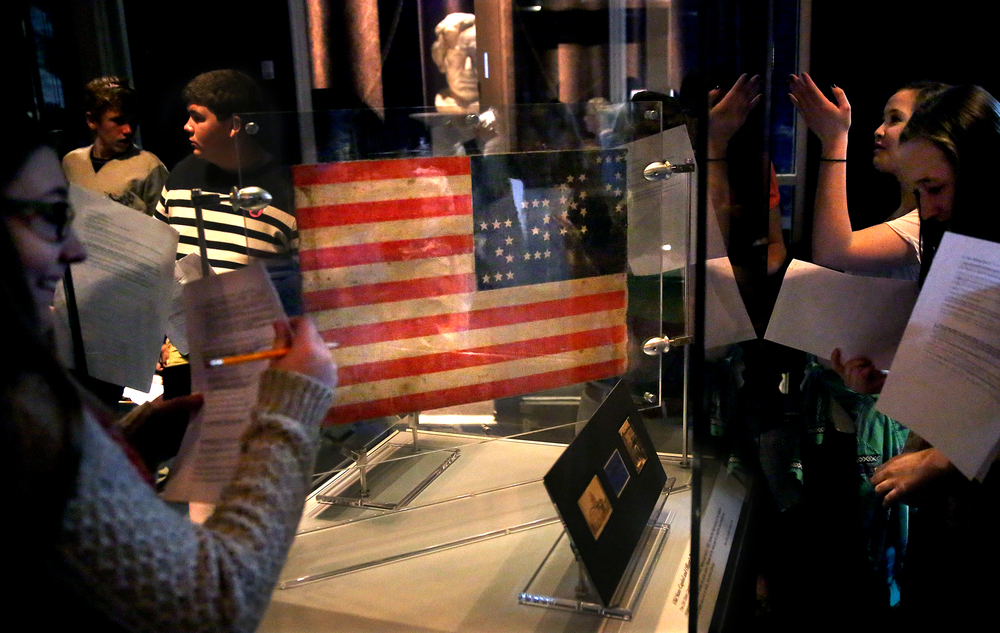 "With a 35-star U.S. flag that Daniel Bower flew from his sandwich cart during the Springfield funeral of Abraham Lincoln at center, Rochester Jr. High School students fill out work sheets on their visit to the museum Thursday morning. The new exhibit  ""A Fiendish Assassination"", opened in the Treasures Gallery at the Abraham Lincoln Presidential Museum in Springfield on April 2, 2015. Running until early July, the more than 40 artifacts displayed-many never before seen in public- show items related to Lincoln's death and funeral 150 years ago this year. David Spencer/The State Journal-Register"