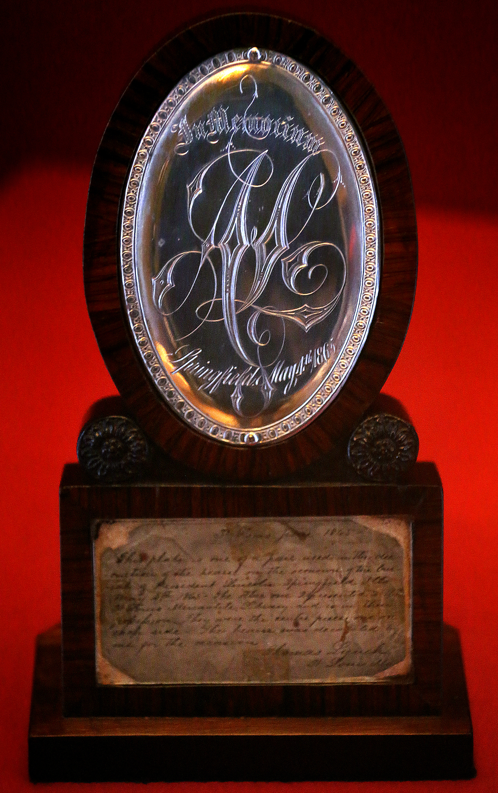 """One of two silver medallions from the hearse that carried Abraham Lincoln to his grave are on display as part of the exhibit. The elaborate gothic script on the medallion reads: In Memoriam A.L. Springfield May 4th 1865.The new exhibit """"A Fiendish Assassination"""", opened in the Treasures Gallery at the Abraham Lincoln Presidential Museum in Springfield on April 2, 2015. Running until early July, the more than 40 artifacts displayed-many never before seen in public- show items related to Lincoln's death and funeral 150 years ago this year. David Spencer/The State Journal-Register"""