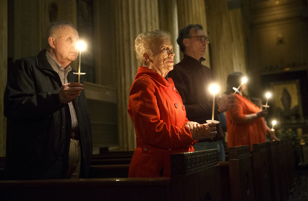 Parishioners hold their candles as the Pascal Candle is brought into the Cathedral of the Immaculate Conception during the Easter Vigil Saturday, April 4, 2015. Ted Schurter/The State Journal-Register