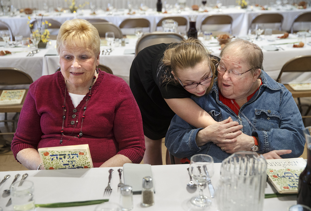 Carly Isaacks hugs her friend Delores Rothschild as her grandmother Barbara Rabin, left, visits with other guests during the Community Passover Seder at Temple B'rith Sholom Saturday, April 4, 2015. Ted Schurter/The State Journal-Register