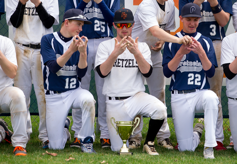 New Berlin's Connor Buehrle, lett, helps Freeport's Connor Bendick, center, learn how to make a pretzel sign with his hands as the teams that share the Pretzels mascot pose for a picture together after the game at New Berlin High School, Tuesday, April 7, 2015, in New Berlin, Ill. Justin L. Fowler/The State Journal-Register