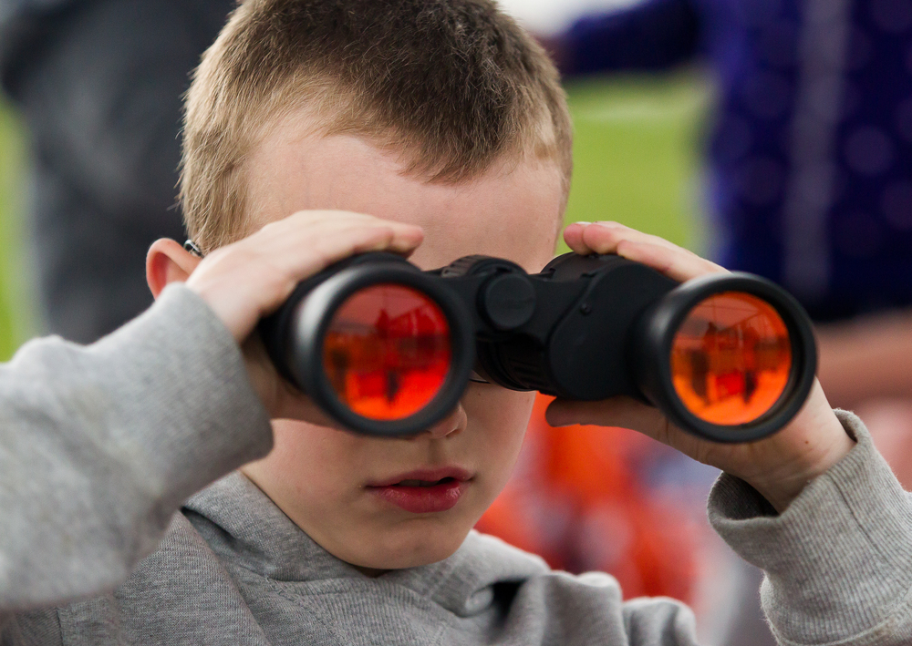 Will Crain, 9, takes in the game from a set of binoculars as he cheers on his favorite New Berlin player, Jake Hunt, as the Pretzels take on the Freeport Pretzels at New Berlin High School, Tuesday, April 7, 2015, in New Berlin, Ill. Justin L. Fowler/The State Journal-Register