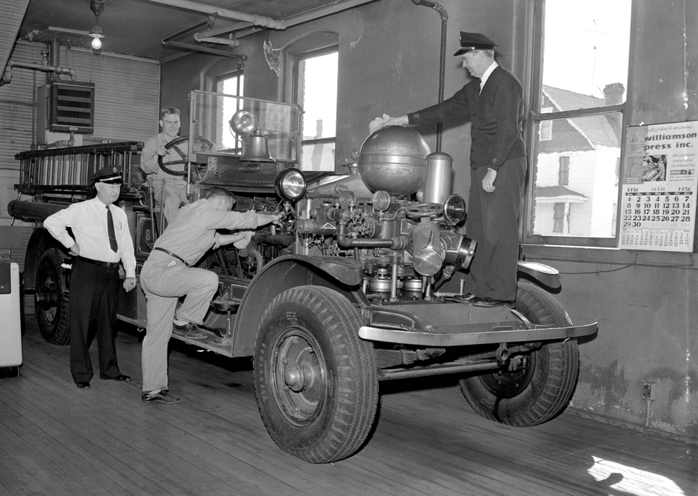 Men working on fire engine, April 4, 1956.