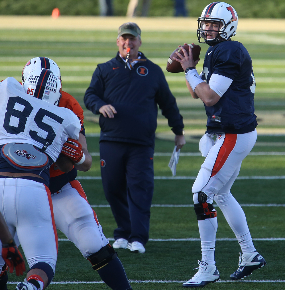 Quarterback Wes Lunt prepares to throw while head coach Tim Beckman looks on from the rear. David Spencer/The State Journal Register