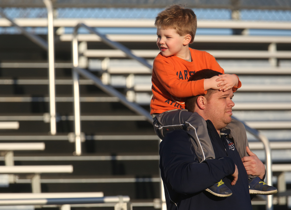 Rochester High School football coach Derek Leonard enjoys the scrimmage from the stand with son Blake Leonard, 4, on his shoulders. Leonard coached Illini quarterback Wes Lunt. David Spencer/The State Journal Register