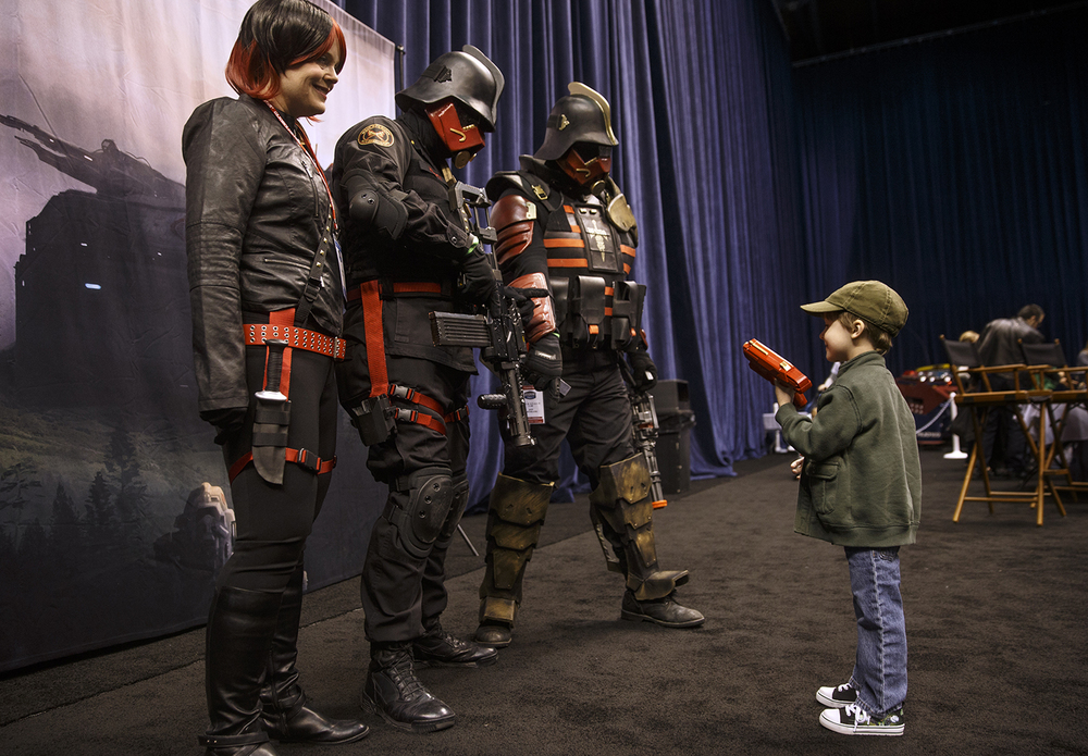 Four-year-old Benjamin Edgecomb of Springfield points his borrowed blaster at a group of Iron Grenadiers, from left, Jenny and Don Maue and Jon Cremeans, before posing for a photograph with them during the official G.I. Joe Collectors' Convention at the Prairie Capital Convention Center Saturday, April 11, 2015. Ted Schurter/The State Journal-Register