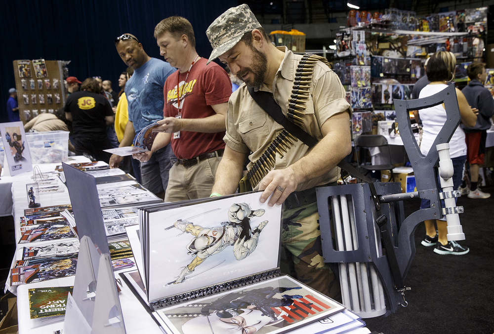 Jim Miel, dressed as the character Rock and Roll version II, flips through artwork on display during the official G.I. Joe Collectors' Convention at the Prairie Capital Convention Center Saturday, April 11, 2015.  Ted Schurter/The State Journal-Register
