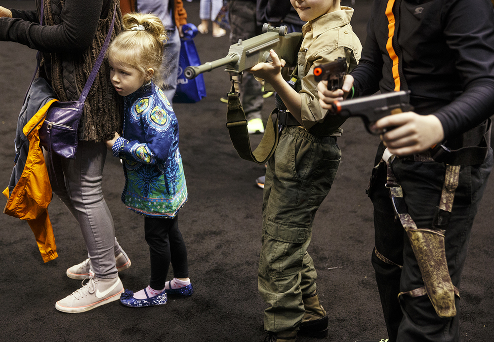 Raeka Armbruster takes shelter behind her mom Mila as participants at the official G.I. Joe Collectors' Convention face off with weapons drawn at the Prairie Capital Convention Center Saturday, April 11, 2015.  Ted Schurter/The State Journal-Register