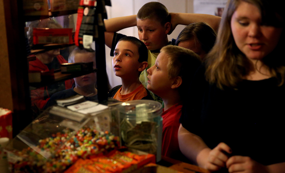 Children waiting in line at the concession stand check out the candy offerings inside a glass display case before putting in their order. David Spencer/The State Journal-Register