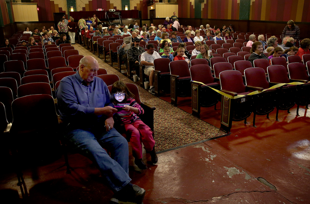Six-year-old Olivia Bitner says busy with a hand-held video game while seated in the front row with grandfather Van Bitner before the start of the show. David Spencer/The State Journal-Register