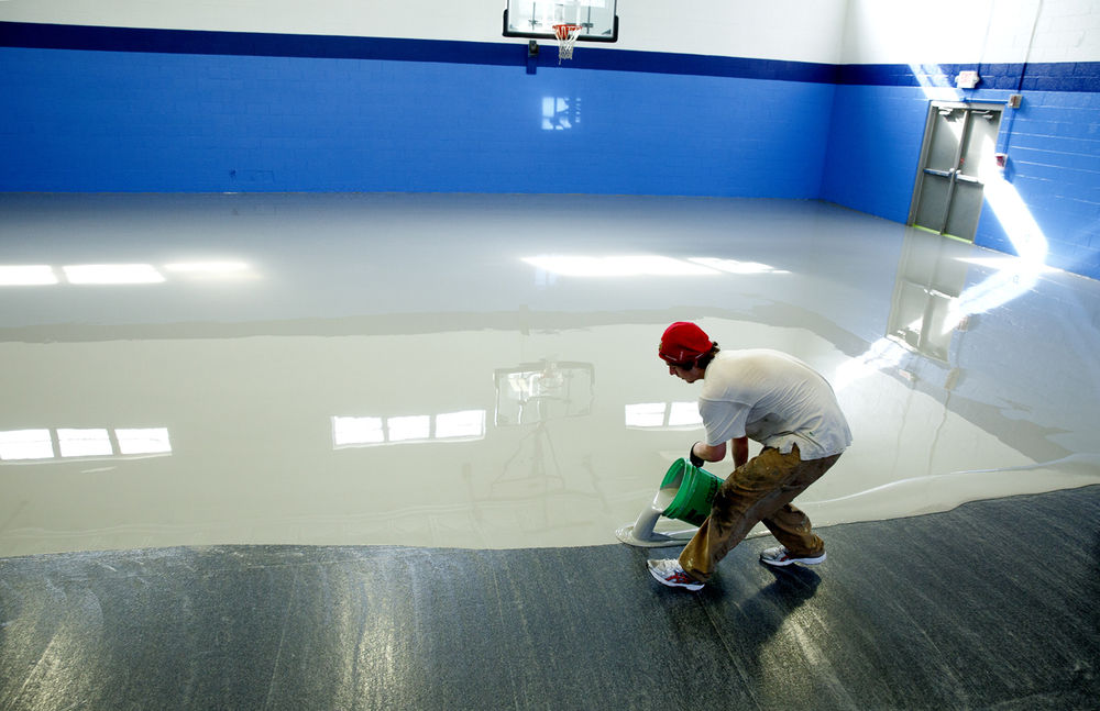 James Roever pours a liquid urethane material on the floor of the gymnasium at the Boys & Girls Club of Springfield Wednesday, April 8, 2015. The self-leveling material will form the base of the new floor, part of a $118,000 improvement to the gymnasium that includes repairs to masonry, new paint, ceiling fans, a drinking fountain and bleachers. Roever works for North American Specialty Flooring, the installation contractor. Once dry, a sealer coat is applied and the lines for a basketball court will painted on the floor. According to Bill Legge, executive director, the floor will be ready to play on in two weeks. Rich Saal/The State Journal-Register