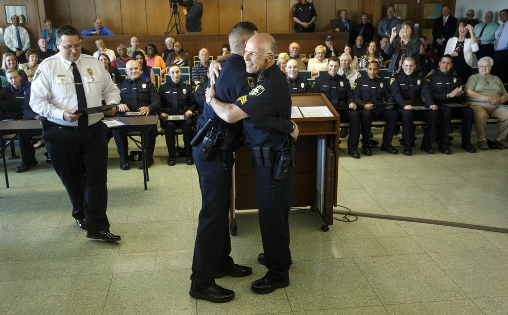 John Von Behren gets a hug from his father Sgt. Rich Von Behren with the Springfield Police Department during a swearing-in ceremony in the City Council Chambers Wednesday, April 15, 2015. Twelve new officers were sworn in. Ted Schurter/The State Journal-Register
