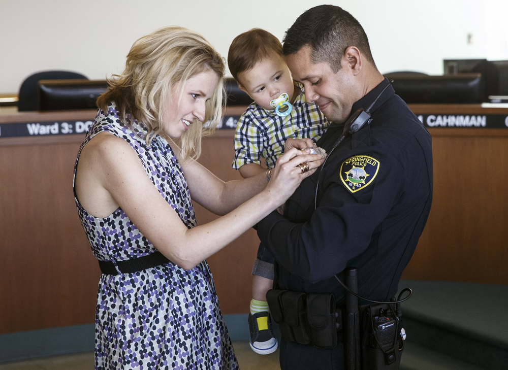 Natalia Rosario pins a badge on her husband Samuel as their son Maksym looks on during a swearing-in ceremony in the City Council Chambers Wednesday, April 15, 2015. Twelve new officers were sworn in. Ted Schurter/The State Journal-Register