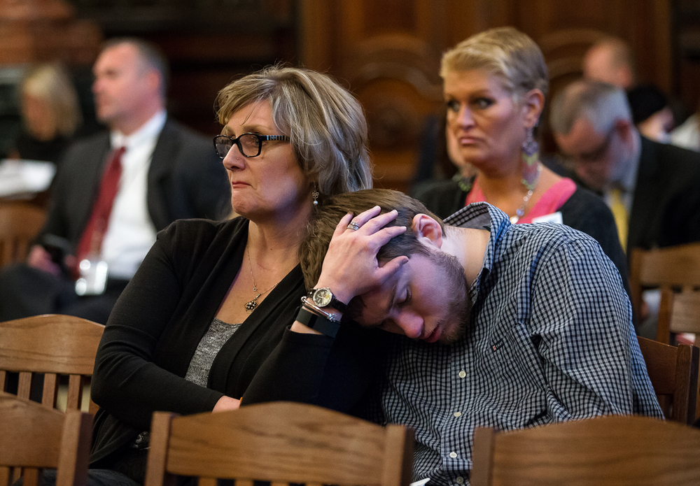 "Seamus McLoughlin, right, leans his head on the shoulder of his mother, Jane McLoughlin, of Palos Heights, Ill., as she listens to testimony on the freezing of $26 million in social services and public health grants during a joint Senate Appropriations I & II Committee Hearing at the Illinois State Capitol, Tuesday, April 14, 2015, in Springfield, Ill. Jane McLoughlin was attending the hearings with the group ""I Am Who I Am"" to help support groups that her son Seamus, who has Autism, benefited from in his youth.  Justin L. Fowler/The State Journal-Register"