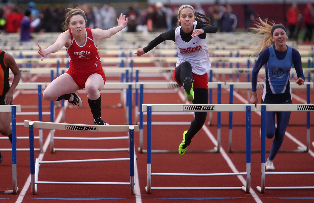 Effingham's Camryn Heuerman at left, who had been leading the girls 100 meter hurdles race, failed to clear the final hurdle which gave the victory to Glenwood's Alicia Windisch at center.  David Spencer/The State Journal-Register