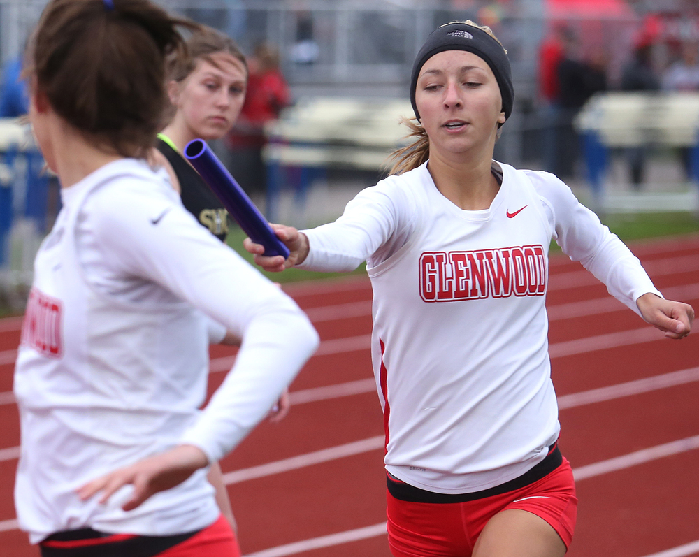 The girls 4 x 800 meter relay event was won by Glenwood. Here, Kerraline Wurl at right hands off the baton to Taylor Justison who ran the final leg.  David Spencer/The State Journal-Register