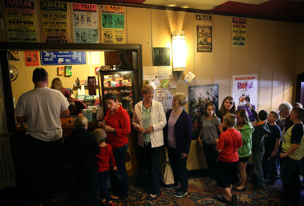 "With original movie posters advertising films shown at the Arlee from the 1940's-1970's tacked to the wall above them, patrons line up at the concession stand inside the lobby before heading for their seats. The Arlee Theater in Mason City, originally a garage built in 1936 and transformed into an Art Deco movie house after being purchased by Art and Leah Struck the same year, has recently been restored. In 2003, John and Gaye Maxson became the new owners and after a 3 month renovation earlier this year, including reupholstery for the 346 seats and the purchase of a brand new $35,000 digital projector paid entirely by community donations, the Arlee officially re-opened for business on Saturday afternoon, April 10, 2015 with a showing of the movie ""The Wizard of Oz"". David Spencer/The State Journal-Register"