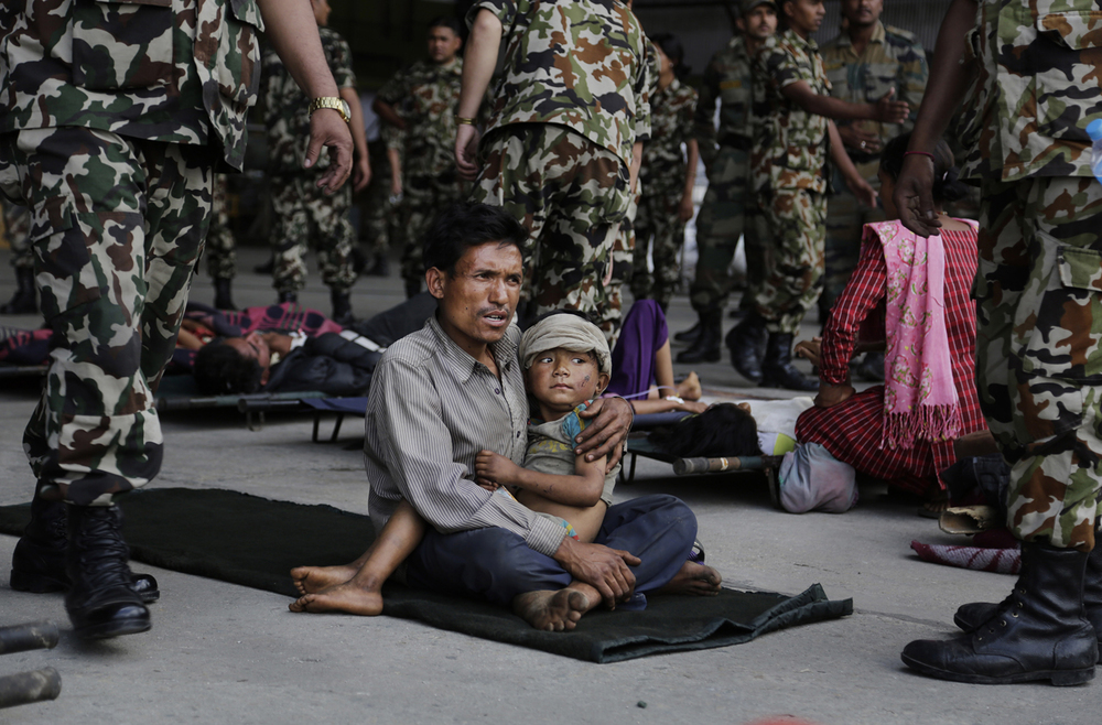 Victims of Saturday's earthquake wait for ambulances after being evacuated at the airport in Kathmandu, Nepal, Monday, April 27, 2015. (AP Photo/Altaf Qadri)