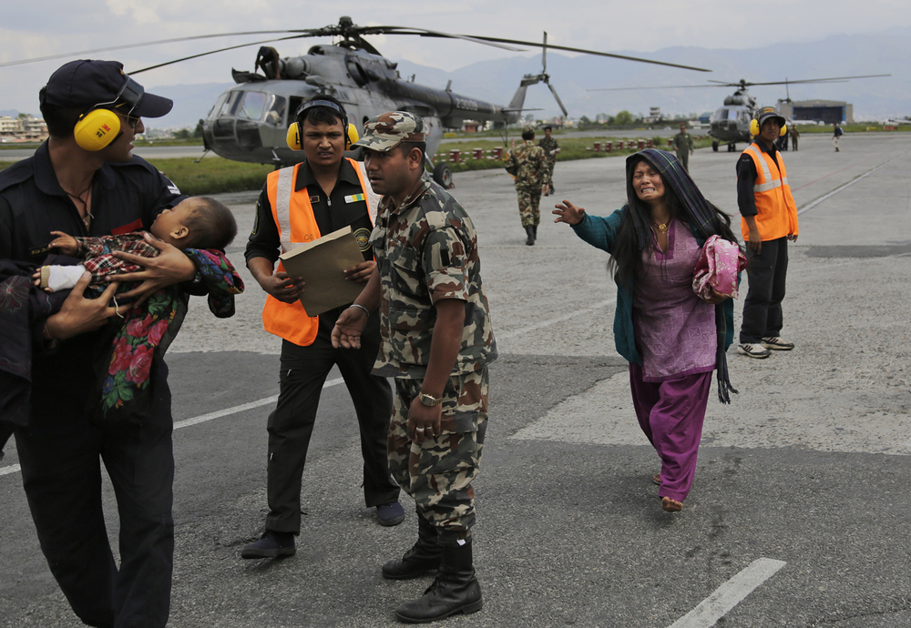 An Indian Air Force person walks carrying a Nepalese child, wounded in Saturday's earthquake, to a waiting ambulance as the mother rushes to join after they were evacuated from a remote area at the airport in Kathmandu, Nepal, Monday, April 27, 2015. (AP Photo/Altaf Qadri)