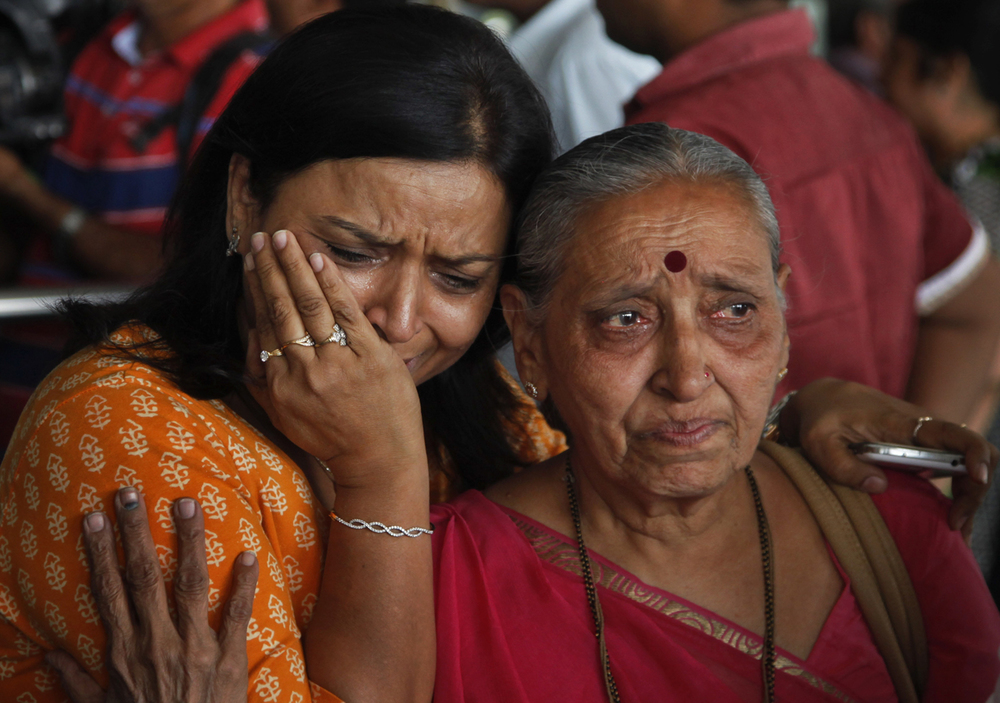 An Indian woman cries as her relative, right who was on pilgrimage in Nepal during Saturday's earthquake, returned at the airport in Ahmadabad, India, Monday, April 27, 2015. (AP Photo/Ajit Solanki)