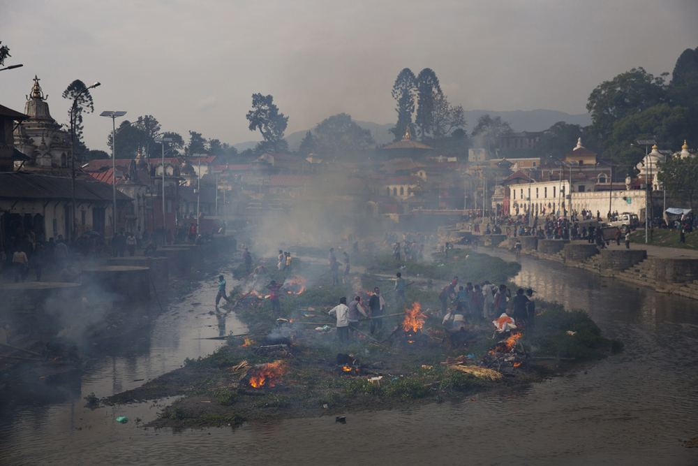 Flames rise from burning funeral pyres during the cremation of victims of Saturday's earthquake, at the Pashupatinath temple on the banks of Bagmati river, in Kathmandu, Nepal, Sunday, April 26, 2015. (AP Photo/Bernat Armangue)